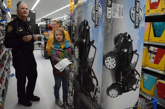 Annie Kornmeyer, 10, of Marshall pushed a cart as Chief Carter Bright from the Tribal Police and his wife, Jennifer Bright from Battle Creek Police Department help look for gifts.
