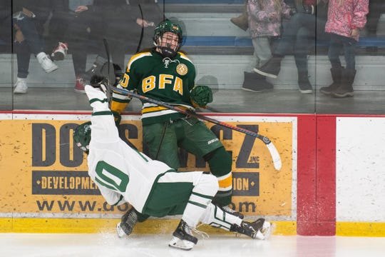 BFA's Matt Merrill (10) and Rice's Garrett Micciche (10) collide against the boards during the boys hockey game between the BFA St. Albans Bobwhites and the Rice Green Knights at Cairns Arena on Saturday night December 14, 2019 in South Burlington, Vermont.