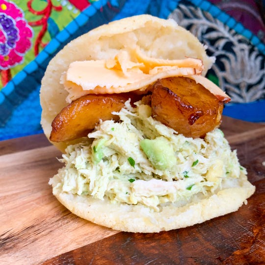 The Curvy Queen is a famous Venezuelan arepa named for a 1950s' beauty pageant star. It features shredded chicken, fried plantains, avocado salad and smoked Gouda.