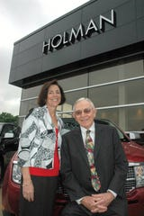 Joseph S. Holman and his daughter Mindy are shown outside a Holman dealership in a 2009 file photo.
