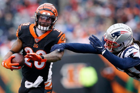 Cincinnati Bengals running back Joe Mixon (28) runs from New England Patriots cornerback Stephon Gilmore (24) on a carry in the fourth quarter of the NFL Week 15 game between the Cincinnati Bengals and the New England Patriots at Paul Brown Stadium in downtown Cincinnati on Sunday, Dec. 15, 2019. The Bengals continued on their path to the No. 1 draft pick with a 34-13 loss to the Patriots.