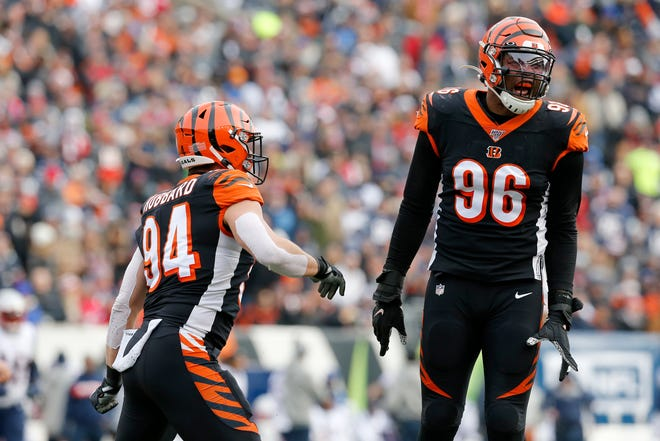 Cincinnati Bengals defensive end Carlos Dunlap (96) and defensive end Sam Hubbard (94) celebrate a strop in the first quarter of the NFL Week 15 game between the Cincinnati Bengals and the New England Patriots at Paul Brown Stadium in downtown Cincinnati on Sunday, Dec. 15, 2019. The Patriots led 13-10 at the half.