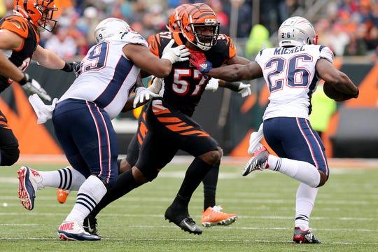 Cincinnati Bengals linebacker Germaine Pratt (57) tracks New England Patriots running back Sony Michel (26) during the second quarter of an NFL Week 15 game, Sunday, Dec. 15, 2019, at Paul Brown Stadium in Cincinnati.