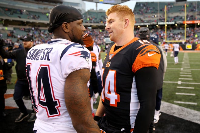 Cincinnati Bengals quarterback Andy Dalton (14) talks with former Bengals and current New England Patriots wide receiver Mohamed Sanu (14), left, at the conclusion NFL Week 15 game, Sunday, Dec. 15, 2019, at Paul Brown Stadium in Cincinnati. The New England Patriots won 34-13.