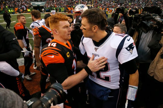 Cincinnati Bengals quarterback Andy Dalton (14) and New England Patriots quarterback Tom Brady (12) shake hands after the fourth quarter of the NFL Week 15 game between the Cincinnati Bengals and the New England Patriots at Paul Brown Stadium in downtown Cincinnati on Sunday, Dec. 15, 2019. The Bengals continued on their path to the No. 1 draft pick with a 34-13 loss to the Patriots.