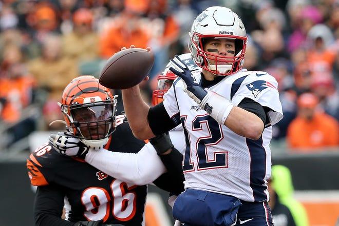 New England Patriots quarterback Tom Brady (12) throws as Cincinnati Bengals defensive end Carlos Dunlap (96) applies pressure during the second quarter of an NFL Week 15 game, Sunday, Dec. 15, 2019, at Paul Brown Stadium in Cincinnati.