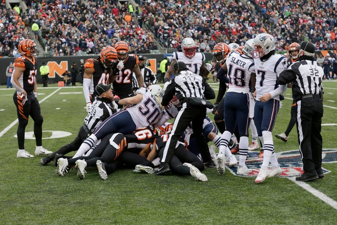 Players dive on a loose ball as Cincinnati Bengals wide receiver Alex Erickson (12) fumbles a punt in the second quarter of the NFL Week 15 game between the Cincinnati Bengals and the New England Patriots at Paul Brown Stadium in downtown Cincinnati on Sunday, Dec. 15, 2019. The Patriots led 13-10 at the half.