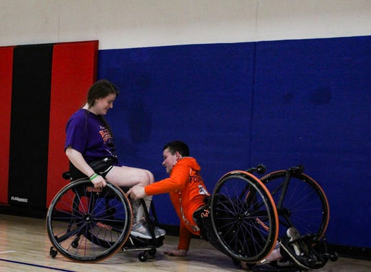 Jenna Fielder, 16, helps up teammate AJ Fitzpatrick, 15, at the Dec. 14 Rolling Panthers practice. Parents learned that during a game the referee will not help a fallen player up and the game continues as they learn to help themselves.