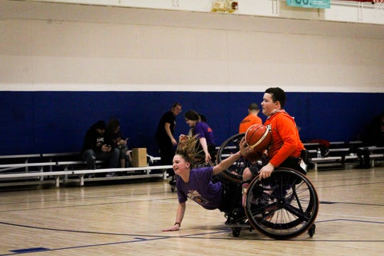 Hannah Becker, the sister of a Rolling Panthers paraplegic basketball team member, often gets in a sport adaptive wheelchair and plays with the team. When players fall, like Becker did here during practice Dec. 14, they are supposed to get up on their own unless seriously injured.