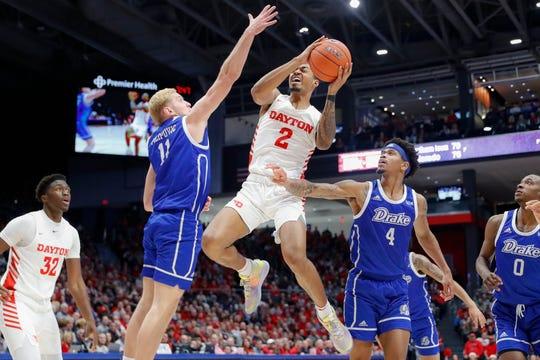 Dayton's Ibi Watson (2) shoots against Drake's Antonio Pilipovic (11) and Anthony Murphy (4) during the first half of an NCAA college basketball game, Saturday, Dec. 14, 2019, in Dayton, Ohio. (AP Photo/John Minchillo)