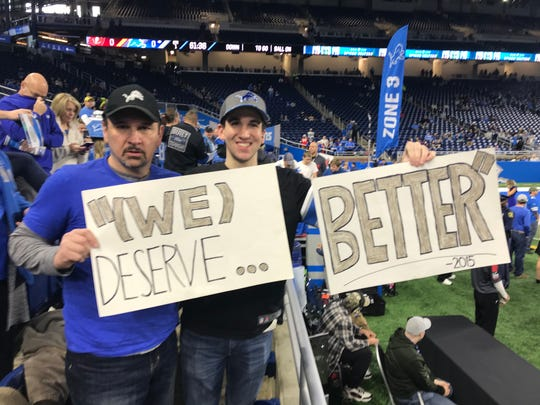 (From left) Greg Smith, 56, and his son, Matthew, 22, from Royal Oak, hold up their signs before the Lions' game against the Buccaneers at Ford Field on Sunday, Dec. 15, 2019.