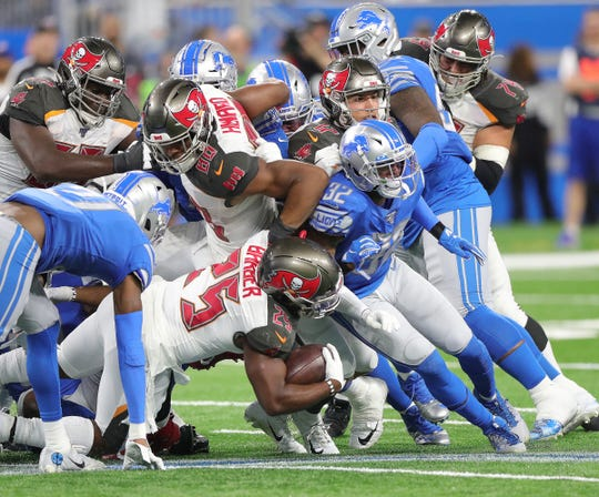 Detroit Lions defenders stop Tampa Bay Buccaneers running back Peyton Barber on fourth down during the second half Sunday, Dec. 15, 2019 at Ford Field.