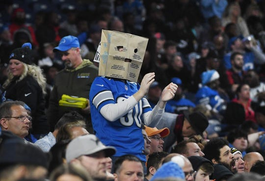A Lions jersey wearing fan completes the fashion statement with a paper grocery bag on his head during the 38-17 loss to Tamp Bay.