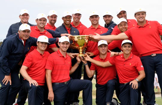 The U.S. players hold their trophy after they won the Presidents Cup.