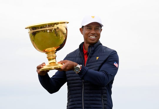 U.S. team player and captain Tiger Woods holds up the trophy after the U.S. team won the Presidents Cup.