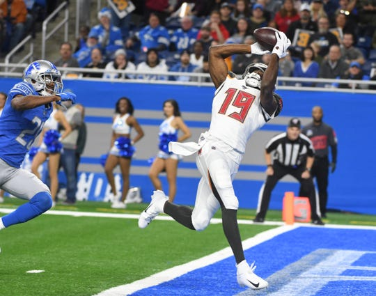 Buccaneers' Breshad Perriman pulls in a touchdown reception on the run with Lions' Rashaan Melvin defending in the first quarter.