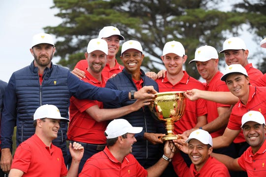 U.S. team player and captain Tiger Woods, center, holds the trophy with his players after the U.S. team won the Presidents Cup.