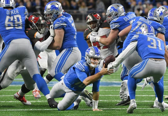Lions quarterback David Blough trips and tosses the ball back to running back Ty Johnson in the first quarter.