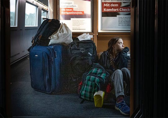 """In this image taken from Twitter feed of Climate activist Greta Thunberg, she's shown sitting on the floor of a train surrounded by bags Saturday, with a comment on overcrowded trains and """"I'm finally on my way home!."""""""