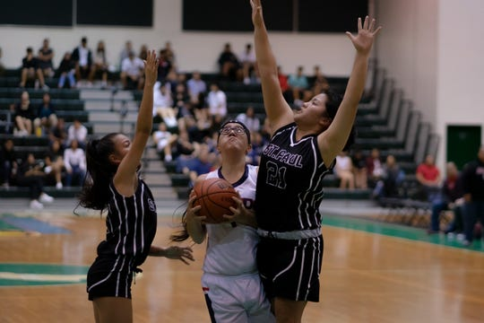 Angeli Dacanay, sandwiched between defenders, a senior at Okkodo High, is co-Most Valuable Player for 2019 IIAAG Girls Basketball.