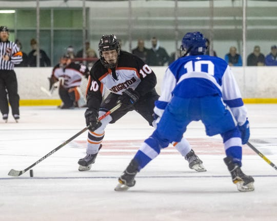 Brighton's Will Jentz carries the puck into the Detroit Catholic Central zone against defenseman Eli Brown on Saturday, Dec. 14, 2019.