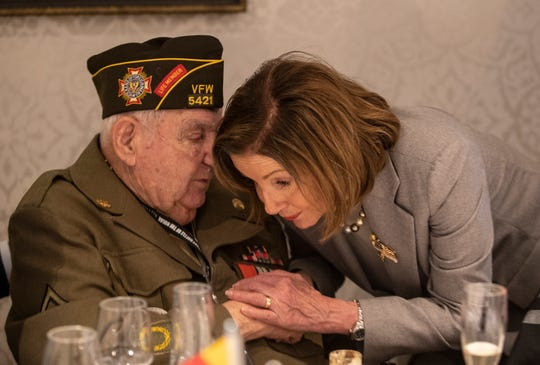 Speaker of the House Nancy Pelosi leans in close to George Merz to better hear what he is saying while attending a luncheon for the 75th anniversary of the Battle of the Bulge. Dec. 14, 2019