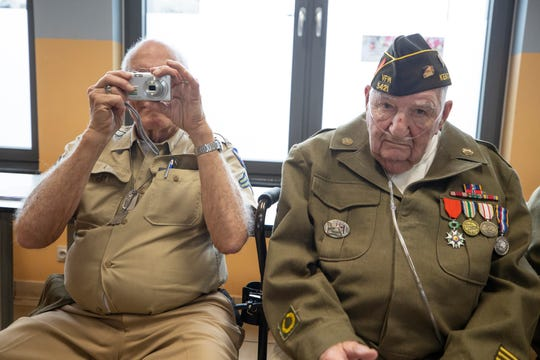 World War II veteran Frank Riesinger takes a photo while fellow vet and Louisville native George Merz looks straight ahead during a visit to the Noville, Belgium Public School. Dec. 14, 2019