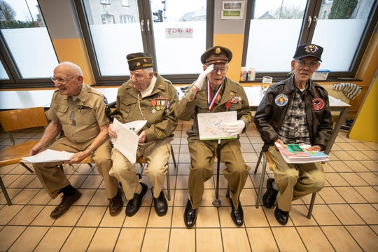 John Pildner Sr. salutes the school children of the Noville, Belgium Public School during a visit as part of the 75th Anniversary of the Battle of the Bulge. From left to right are, Frank Riesinger, George Merz, of Louisville, Pidner and Robert Izumi a Vietnam veteran. Dec. 13, 2019