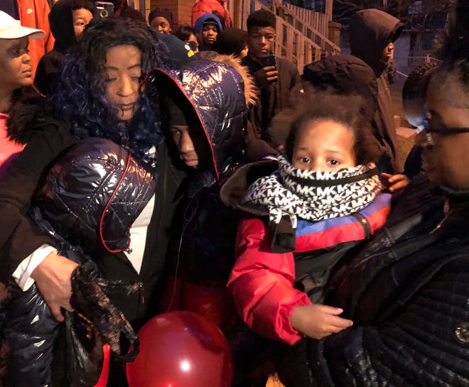 The grandmother of 15-year-old homicide victim Jason Eggars consoles two of Jason's younger brothers, Nivaire, 13, and Jivyon, 10, at a vigil Saturday night outside the family's home. A family friend holds the boys' baby brother Shawn.