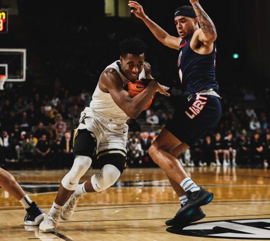 Vanderbilt's Aaron Nesmith drives the ball against a Liberty defender at Memorial Gym on Saturday, Dec. 14, 2019.
