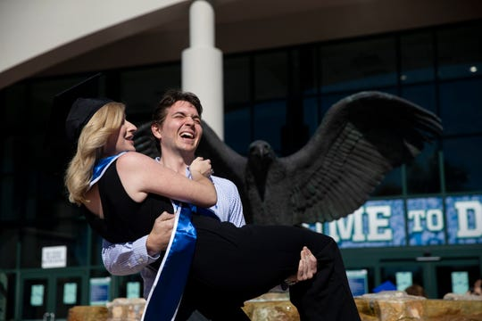 Tom Bakoczy lifts Alicia Boterl to his chest during Florida Gulf Coast University's 2019 commencement ceremony on Sunday, December 15, 2019, at Alico Arena in Estero.