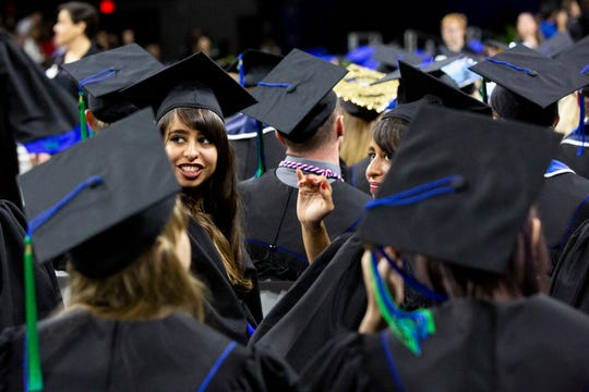 The graduates wave to their family during the 2019 commencement ceremony on Sunday, December 15, 2019, at Alico Arena in Estero.