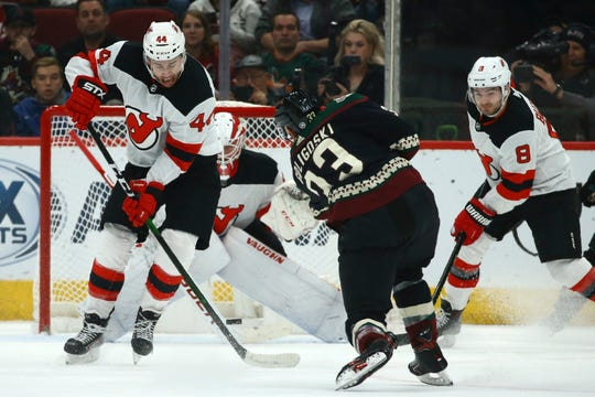 Arizona Coyotes defenseman Alex Goligoski (33) sends a shot past New Jersey Devils left wing Miles Wood (44), Devils defenseman Will Butcher (8) and Devils goaltender Mackenzie Blackwood, middle, for a goal during the first period of an NHL hockey game, Saturday, Dec. 14, 2019 in Glendale, Ariz.