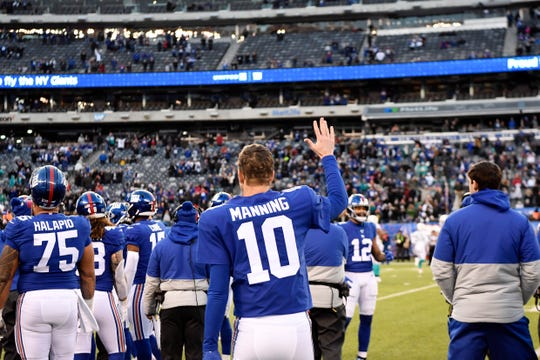 New York Giants quarterback Eli Manning (10) waves to the crowd as fans chant his name at the end of the game. The Giants defeat the Dolphins 36-20 on Sunday, Dec. 15, 2019, in East Rutherford.