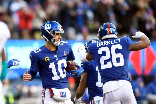 New York Giants quarterback Eli Manning (10) and running back Saquon Barkley (26) celebrate a touchdown against the Miami Dolphins as Manning holds the football caught by wide receiver Golden Tate (not pictured) in the first half of an NFL game on Sunday, Dec. 15, 2019, in East Rutherford.