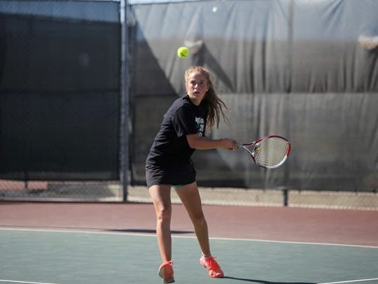 Farmington's Rachel Kelly follows through with a backhand return against Gallup during girls singles on Saturday, April 21, 2018 at Farmington Tennis Complex. The Lady Scorpions won six team championships during the 2010s.