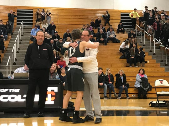 Troy head boys basketball coach Gary Fralick hugs his grandson Bryce Lubin prior to the game against Novi.