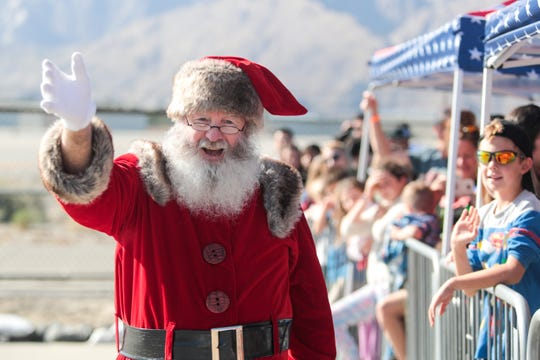 Santa Claus waves to children at the Palm Springs Air Museum on Sunday, December 15, 2019.