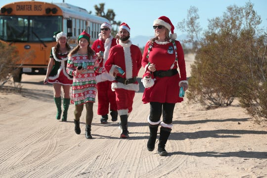 SantaCon organizer Heather Vescent, front, leads the way to the groups second stop of the day, at Noah Purifoy Desert Art Museum, as part of the first SantaCon event in Joshua Tree, Calif., on Saturday, December 14, 2019.