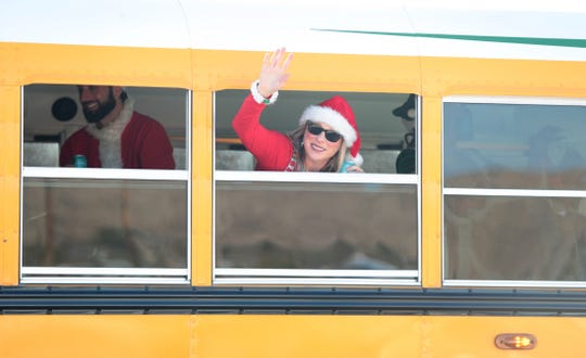 SantaCon organizer Heather Vescent waves from the chartered school bus as part of the first SantaCon in Joshua Tree, Calif., on Saturday, December 14, 2019.