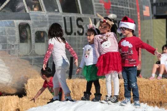 Children play in the snow at the Palm Springs Air Museum on Sunday, December 15, 2019.