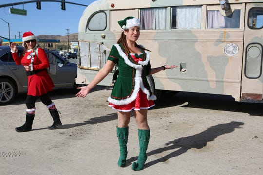 SantaCon organizer Heather Vescent, left, watches as Natasha Shelby tries to get people to come join the first SantaCon event in Joshua Tree, Calif., on Saturday, December 14, 2019.