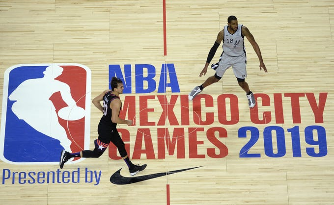 Dec 14, 2019; Mexico City, MEX; Phoenix Suns forward Dario Saric (20) and San Antonio Spurs center LaMarcus Aldridge (12) run down court past the Mexico City Games 2019 logo at mid court during the third quarter at Mexico City Arena. Mandatory Credit: Orlando Ramirez-USA TODAY Sports