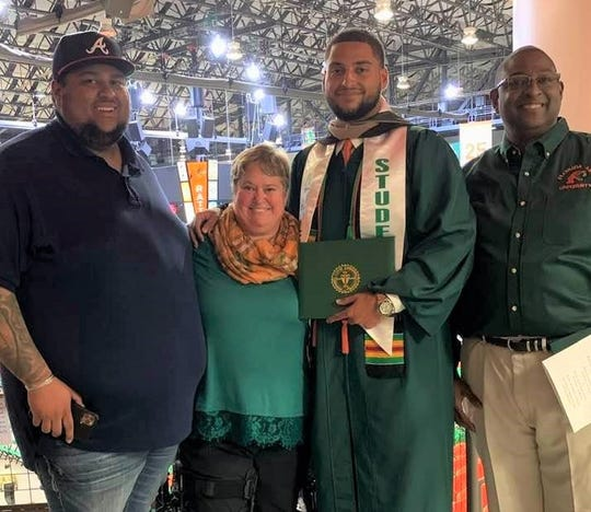 Jay Saffold (left), Jeannie Saffold and Stacy Saffold (far right) share in the celebratory moment with FAMU offensive lineman Zach Saffold during the fall commencement ceremony on Friday, Dec. 13, 2019.