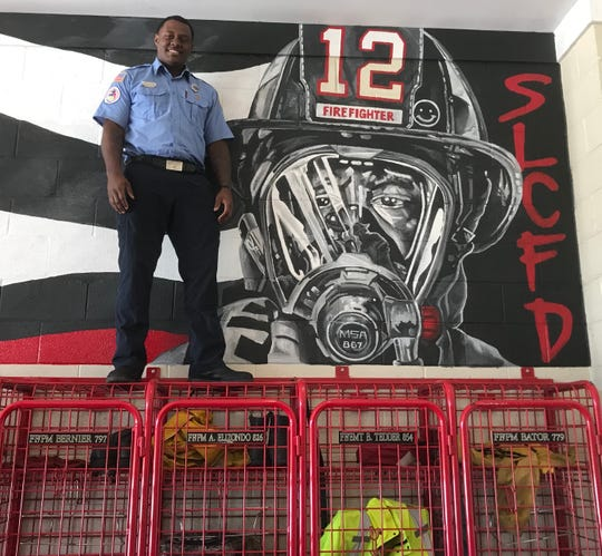 Firefighter Julian Reams stands by a mural he painted