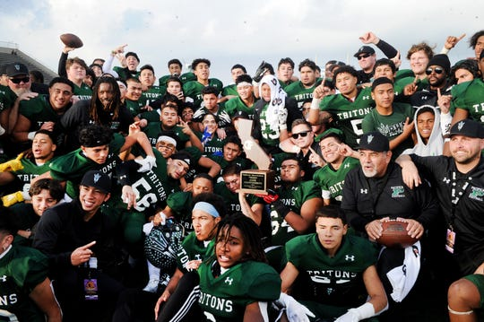 The Pacifica High football team poses with the state trophy after beating McClymonds 34-6 in the CIF Division 2-A state championship bowl at Cerritos College in Norwalk on Saturday afternoon. The Tritons became the first local public school to win a state title in football.