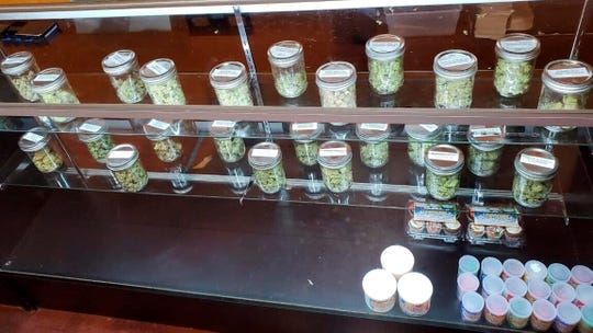 This Dec. 12, 2019 photo provided by the Department of Consumer Affairs shows a display with jars of marijuana at Save Greens Cannabis dispensary in Los Angeles.