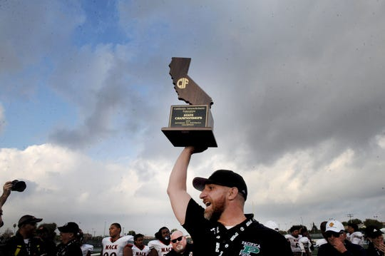 Pacifica High head coach Mike Moon hoisted the state trophy after the Tritons beat McClymonds 34-6 in the CIF Division 2-A state championship bowl at Cerritos College in Norwalk on Saturday.
