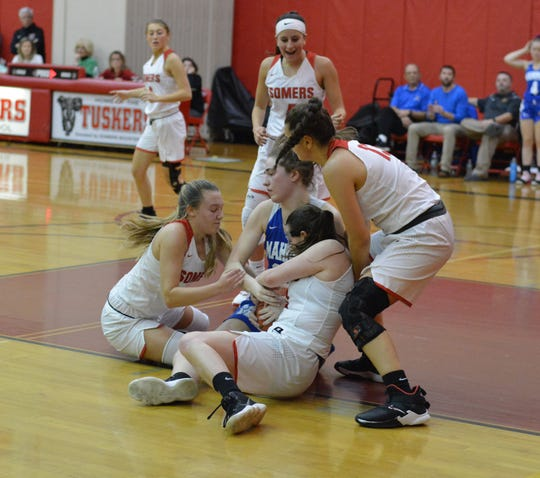 Mahopac forward Caitlyn O'Boyle battles with Amy Lasher (left), Emily Arena and Jordan May for a loose ball during the consolation game of the Michael DePaoli Memorial Basketball Tournament at Somers High School on Dec. 14, 2019. The Indians hung on to win 51-46.