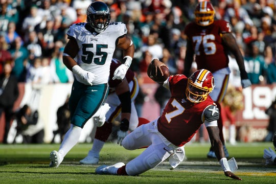 Washington Redskins quarterback Dwayne Haskins (7) loses his footing while running with the ball in the first half of an NFL football game against the Philadelphia Eagles, Sunday, Dec. 15, 2019, in Landover, Md. Giving chase is Philadelphia Eagles defensive end Brandon Graham (55). (AP Photo/Patrick Semansky)